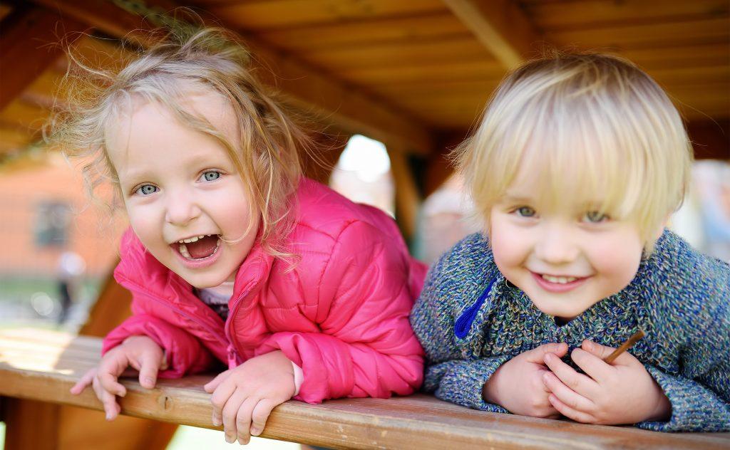 Happy kids having fun on outdoor playground. Spring/summer/autumn active sport leisure for children. Portrait of little boy and girl playing on kindergarten backyard